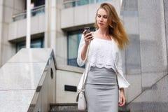 Junge Geschäftsfrau, die auf Mobiltelefon beim Gehen im Freien spricht Lizenzfreies Stockbild