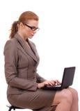 Junge Geschäftsfrau, die auf Stuhl mit Laptop sitzt Lizenzfreie Stockfotos
