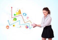 Junge Geschäftsfrau, die bunte Diagramme und Diagramme darstellt lizenzfreies stockfoto
