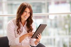 Junge Geschäftsfrau, die den Tablet-Computer schaut zur Kamera verwendet Lizenzfreie Stockfotos