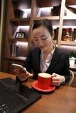 Junge Geschäftsfrau, die in der Kaffeestube am Holztisch, an trinkendem Kaffee sitzt und Smartphone verwendet Auf Tabelle ist Lap Stockbilder