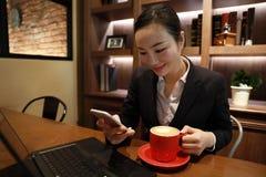 Junge Geschäftsfrau, die in der Kaffeestube am Holztisch, an trinkendem Kaffee sitzt und Smartphone verwendet Auf Tabelle ist Lap Lizenzfreies Stockfoto