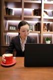 Junge Geschäftsfrau, die in der Kaffeestube am Holztisch, trinkender Kaffee sitzt Auf Tabelle ist Laptop Stockfotografie