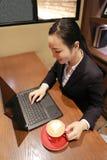 Junge Geschäftsfrau, die in der Kaffeestube am Holztisch, trinkender Kaffee sitzt Auf Tabelle ist Laptop Stockbild
