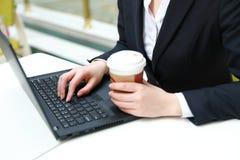 Junge Geschäftsfrau, die in der Kaffeestube am Holztisch, trinkender Kaffee sitzt Auf Tabelle ist Laptop Lizenzfreie Stockbilder