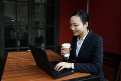 Junge Geschäftsfrau, die in der Kaffeestube am Holztisch, trinkender Kaffee sitzt Auf Tabelle ist Laptop Lizenzfreies Stockfoto