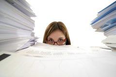 Junge Geschäftsfrau, die in der Schreibarbeit ertrinkt Stockfotografie