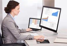 Junge Geschäftsfrau, die Diagramm auf Computer analysiert Stockfotos