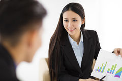 Junge Geschäftsfrau, die Diagramm auf Diagramm im Büro zeigt stockbilder