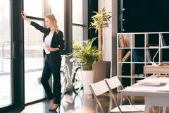 Junge Geschäftsfrau, die digitale Tablette hält und Fenster im modernen Büro betrachtet Stockbilder