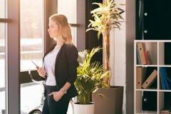 Junge Geschäftsfrau, die digitale Tablette hält und Fenster im modernen Büro betrachtet Lizenzfreie Stockfotografie