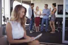 Junge Geschäftsfrau, die digitale Tablette mit dem Team sich bespricht im Hintergrund verwendet Stockfotos