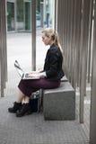 Junge Geschäftsfrau, die draußen mit Laptop sitzt Stockfotos