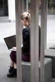 Junge Geschäftsfrau, die draußen mit Laptop sitzt Stockfotografie