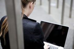 Junge Geschäftsfrau, die draußen mit Laptop sitzt Lizenzfreies Stockbild
