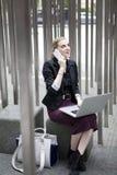 Junge Geschäftsfrau, die draußen mit Laptop und beweglichem Phon sitzt Lizenzfreies Stockfoto