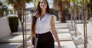 Junge Geschäftsfrau, die durch einen Park geht stock video