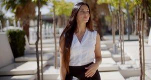 Junge Geschäftsfrau, die durch einen Park geht stock video footage