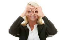 Junge Geschäftsfrau, die durch Finger schaut Lizenzfreie Stockbilder