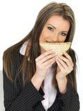 Junge Geschäftsfrau, die ein Lachs-und Gurken-Schwarzbrot-Sandwich halten isst Lizenzfreie Stockfotografie