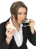 Junge Geschäftsfrau, die ein Speck-Sandwich und einen schwarzen Kaffee isst Stockfotografie