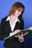 Junge Geschäftsfrau, die eine grüne Datei liest Stockfotos