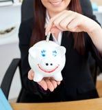Junge Geschäftsfrau, die eine Piggyquerneigung anhält stockbilder