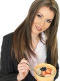 Junge Geschäftsfrau, die eine Schüssel Brei mit frischer Frucht isst Stockbilder