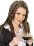 Junge Geschäftsfrau, die eine Schale schwarzen Kaffee trinkt Lizenzfreies Stockbild