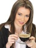 Junge Geschäftsfrau, die eine Schale schwarzen Kaffee trinkt Stockfotos