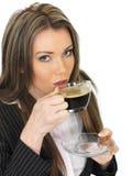 Junge Geschäftsfrau, die eine Schale schwarzen Kaffee trinkt Stockfotografie