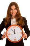 Junge Geschäftsfrau, die eine Uhr lokalisiert in weiß- Zeit hält Stockbild