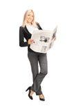Junge Geschäftsfrau, die eine Zeitung hält und an einem wa sich lehnt Lizenzfreies Stockfoto