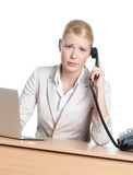 Junge Geschäftsfrau, die an einem Büroschreibtisch mit Telefonhörer sitzt stockfotografie