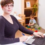 Junge Geschäftsfrau, die an einem Laptop arbeitet Stockbilder