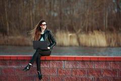 Junge Geschäftsfrau, die an einem Laptop sitzt lizenzfreie stockfotografie