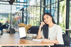 Junge Geschäftsfrau, die einen Bericht ihre Hand hält einen Stift sitzt in einer Kaffeestube liest Stockfotografie