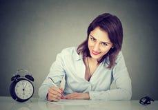 Junge Geschäftsfrau, die einen Brief schreibt oder ein Anmeldeformular ergänzt Stockfoto