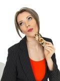 Junge Geschäftsfrau, die einen Frühstücks-Müsliriegel isst Stockfotografie