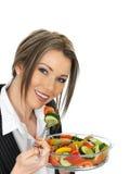 Junge Geschäftsfrau, die einen frischen Mischsalat isst Stockbilder