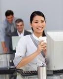 Junge Geschäftsfrau, die einen Kaffee an ihrem Schreibtisch trinkt Stockfotos