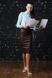 Junge Geschäftsfrau, die einen Laptop, stehend auf Büro hält Stockfotografie