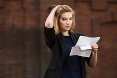 Junge Geschäftsfrau, die einen Steuerbrief in der Stadtstraße liest Lizenzfreie Stockfotografie
