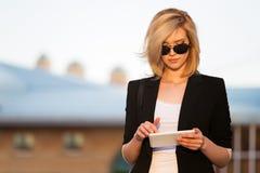 Junge Geschäftsfrau, die einen Tablettecomputer verwendet stockbild