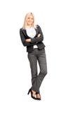 Junge Geschäftsfrau, die an einer Wand sich lehnt Stockbild
