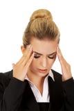 Junge Geschäftsfrau, die enorme Kopfschmerzen hat Stockbild