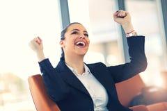 Junge Geschäftsfrau, die Erfolg bei der Arbeit genießt Lizenzfreies Stockbild