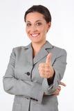 Junge Geschäftsfrau, die Erfolgszeichen zeigt lizenzfreie stockfotografie