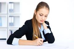 Junge Geschäftsfrau, die etwas Schreibarbeit tut Lizenzfreies Stockfoto