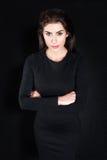 Junge Geschäftsfrau, die gegen schwarzen Hintergrund ernst steht Lizenzfreie Stockfotografie